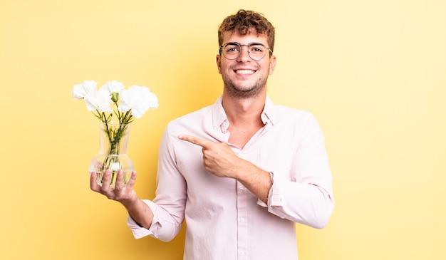 元気に笑って、幸せを感じて、横を指している若いハンサムな男。花のコンセプト