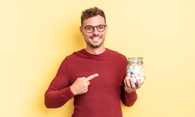 元気に笑って、幸せを感じて、横を指している若いハンサムな男。ゼリーキャンディーのコンセプト