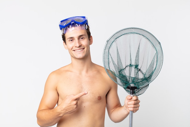 Young handsome man smiling cheerfully, feeling happy and pointing to the side with goggles and a fishing net