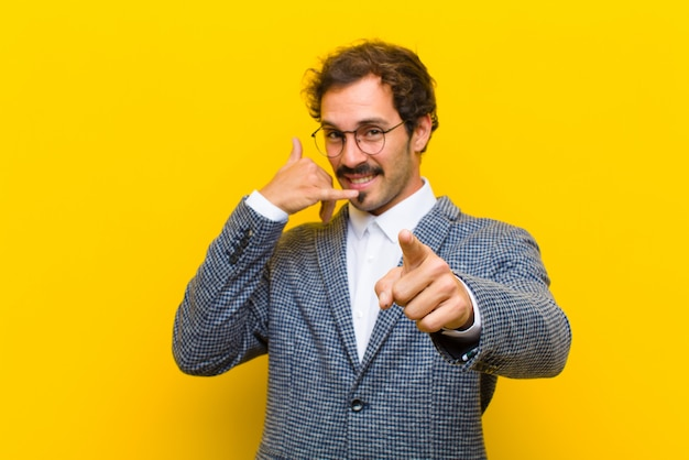 Young handsome man smiling cheerfully and pointing to camera while making a call you later gesture, talking on phone against orange wall