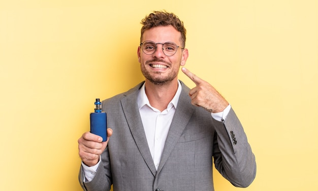 Young handsome man smiling confidently pointing to own broad smile. vaporizer concept