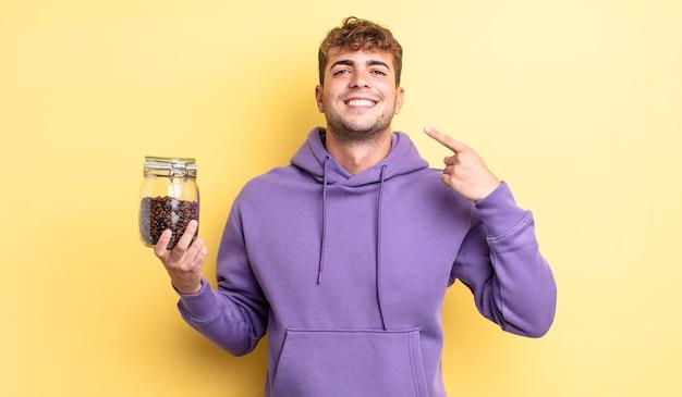 자신의 넓은 미소를 자신있게 가리키며 웃고 있는 잘생긴 청년. 커피 콩 개념