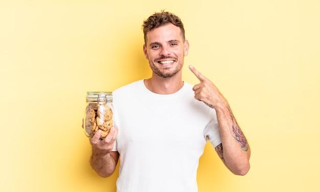 自信を持って笑顔の若いハンサムな男は、自分の広い笑顔のクッキーボトルの概念を指しています