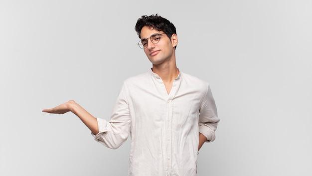 젊은 잘 생긴 남자 미소, 자신감, 성공 및 행복 느낌, 측면에 복사 공간에 개념이나 아이디어를 보여주는