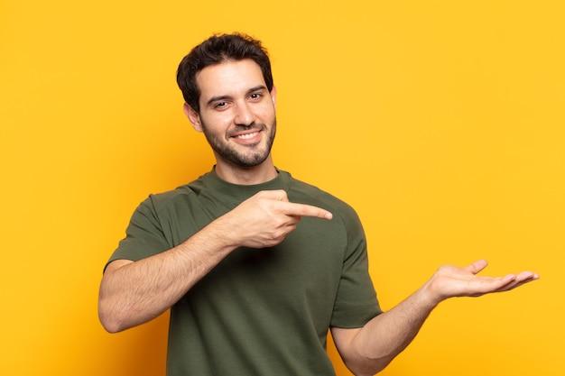 Молодой красивый мужчина улыбается, чувствует себя счастливым, беззаботным и довольным, указывая на концепцию или идею на копировальном пространстве сбоку