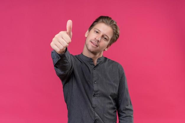 ピンクの壁の上に立ってフレンドリーな表示親指を笑っている若いハンサムな男
