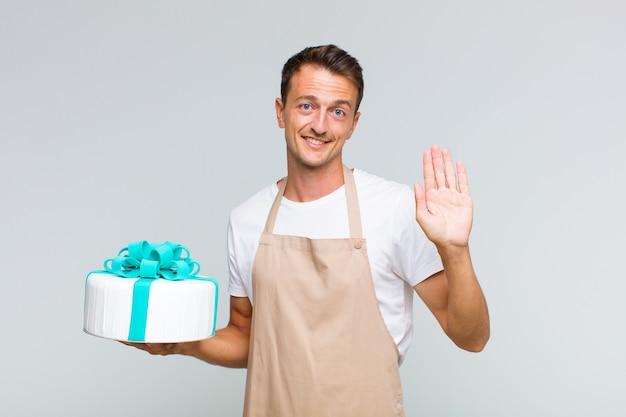행복하고 유쾌하게 웃고, 손을 흔들며, 환영하고 인사하거나, 작별 인사를하는 젊은 잘 생긴 남자
