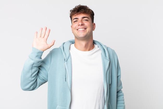 젊고 잘생긴 남자는 행복하고 즐겁게 웃고, 손을 흔들고, 당신을 환영하고 인사하거나 작별 인사를 합니다.