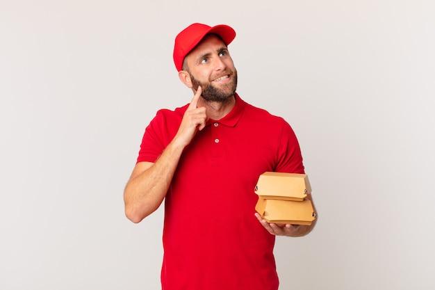 Молодой красивый мужчина счастливо улыбается и мечтает или сомневается в доставке гамбургеров