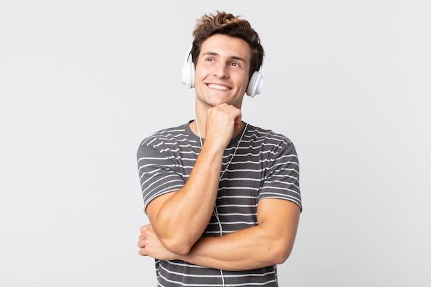 幸せに笑って、空想にふけるか、疑う若いハンサムな男。リスニングミュージックのコンセプト