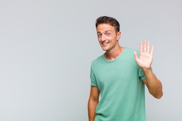 Young handsome man smiling happily and cheerfully, waving hand, welcoming and greeting you, or saying goodbye