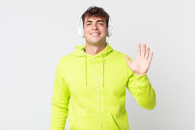 幸せに笑って、手を振って、あなたとヘッドフォンを歓迎し、挨拶する若いハンサムな男