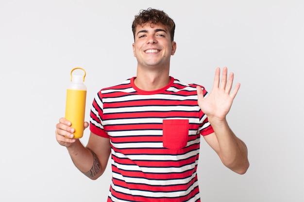 젊고 잘생긴 남자는 행복하게 웃고, 손을 흔들며, 당신을 환영하고 인사하고, 커피 보온병을 들고 있습니다.