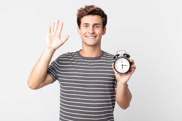 幸せに笑って、手を振って、あなたを歓迎して挨拶し、目覚まし時計を持っている若いハンサムな男