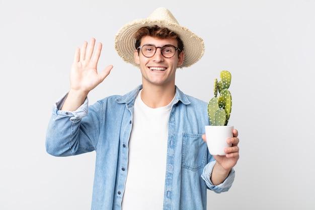 젊고 잘생긴 남자는 행복하게 웃고, 손을 흔들고, 당신을 환영하고 인사합니다. 장식용 선인장을 들고 있는 농부
