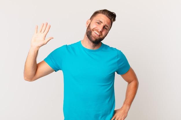 젊고 잘생긴 남자는 행복하게 웃고 손을 흔들며 환영하고 인사합니다. 피트니스 개념