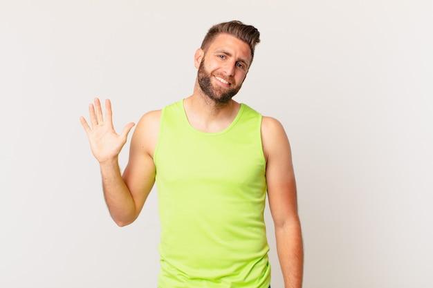 젊고 잘생긴 남자는 행복하게 웃고, 손을 흔들고, 당신을 환영하고 인사합니다. 피트니스 개념