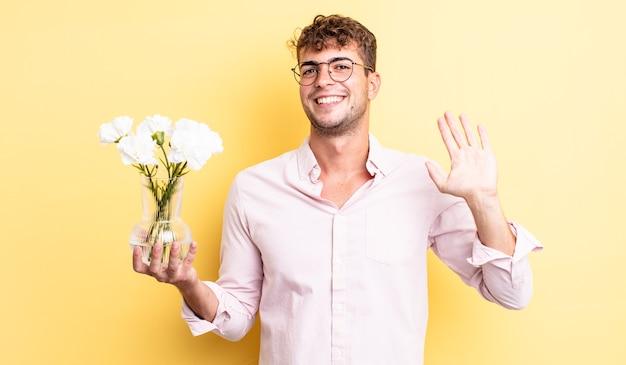 Молодой красивый мужчина счастливо улыбается, машет рукой, приветствует и приветствует вас. концепция цветов