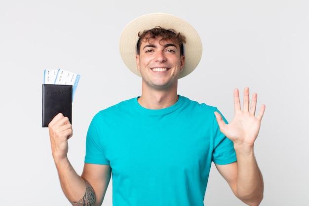 젊고 잘생긴 남자는 행복하게 웃고, 손을 흔들고, 당신을 환영하고 인사합니다. 여권을 들고 있는 여행자
