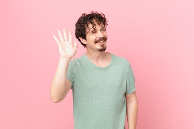 幸せに笑って、手を振って、あなたを歓迎し、挨拶する若いハンサムな男