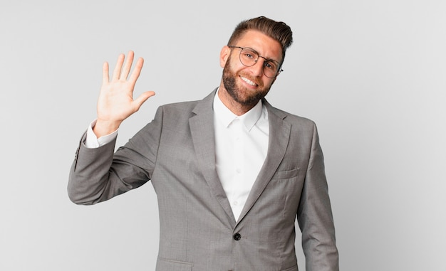Young handsome man smiling happily, waving hand, welcoming and greeting you. business concept