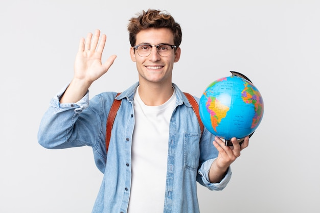 Young handsome man smiling happily, waving hand, welcoming and greeting you. student holding a world globe map