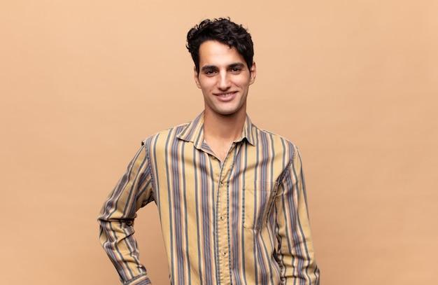Молодой красивый мужчина счастливо улыбается, положив руку на бедро и уверенный, позитивный, гордый и дружелюбный.