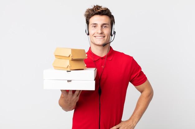 Молодой красивый мужчина счастливо улыбается, положив руку на бедро и уверенно. забрать концепцию быстрого питания