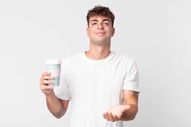 Молодой красивый мужчина счастливо улыбается, дружелюбно предлагает и показывает концепцию и держит кофе на вынос
