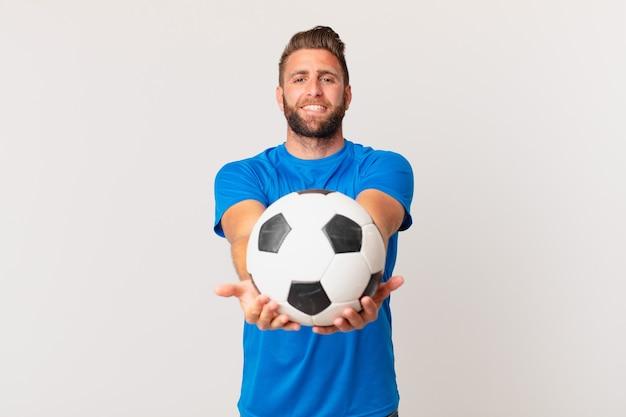 Молодой красивый мужчина, счастливо улыбаясь, дружелюбно предлагая и показывая концепцию. футбольная концепция