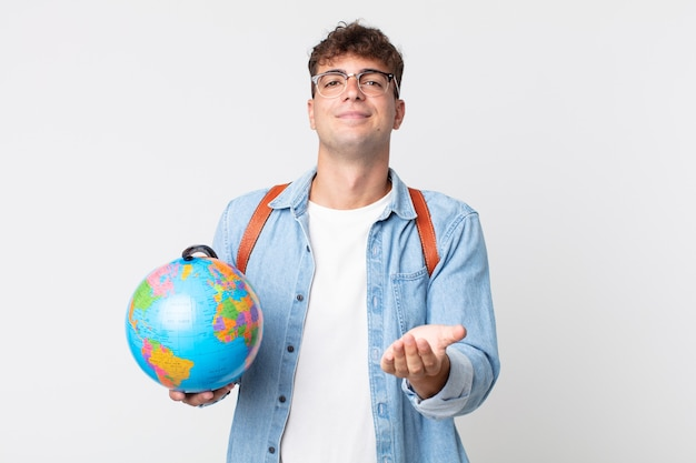 Молодой красивый мужчина, счастливо улыбаясь, дружелюбно предлагая и показывая концепцию. студент держит карту мира