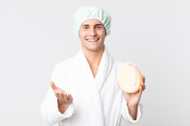 Молодой красивый мужчина счастливо улыбается, дружелюбно предлагает и показывает концепцию с халатом, шапочкой для душа и губкой