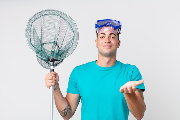 Молодой красивый мужчина счастливо улыбается, дружелюбно предлагает и демонстрирует концепцию с очками и рыболовной сетью