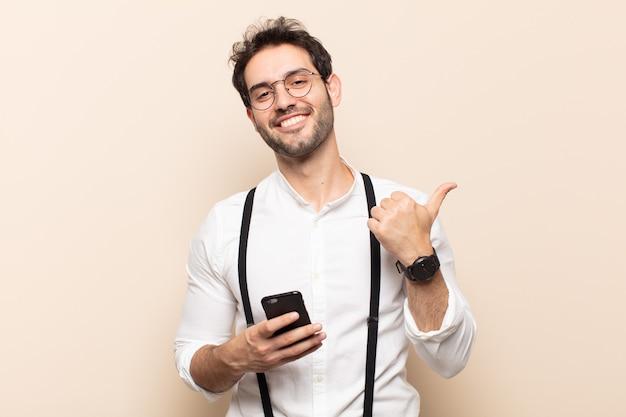 젊고 잘생긴 남자는 즐겁게 웃고 행복해 보이며 두 엄지손가락으로 근심 없고 긍정적인 느낌을 줍니다.