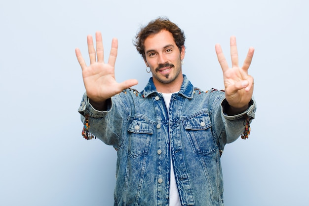 Young handsome man smiling and looking friendly, showing number eight or eighth with hand forward, counting down isolated against flat wall
