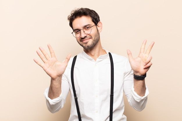 Young handsome man smiling and looking friendly, showing number eight or eighth with hand forward, counting down