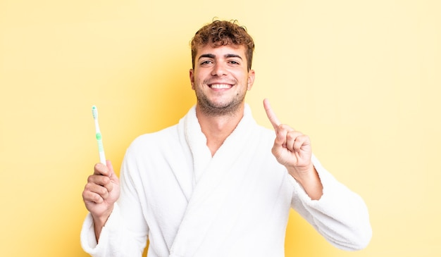 Young handsome man smiling and looking friendly, showing number one. toothbrush concept