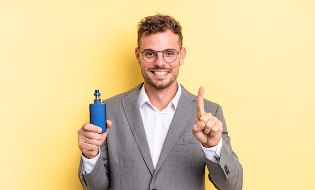Young handsome man smiling and looking friendly, showing number one. vaporizer concept