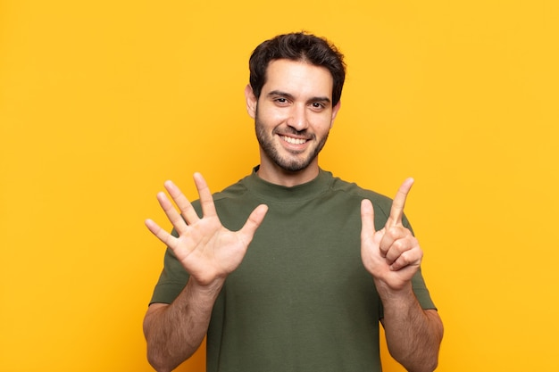 Young handsome man smiling and looking friendly, showing number seven or seventh with hand forward, counting down