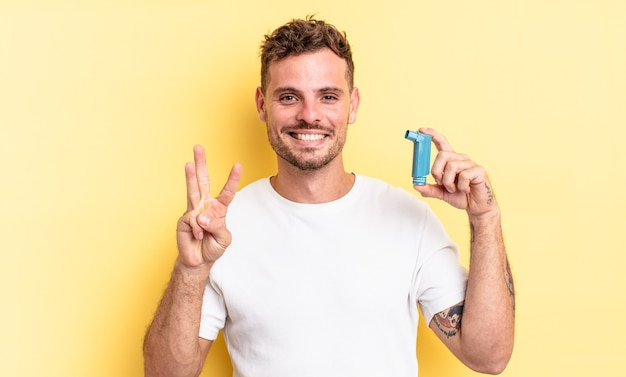 Young handsome man smiling and looking friendly, showing number three. asthma concept