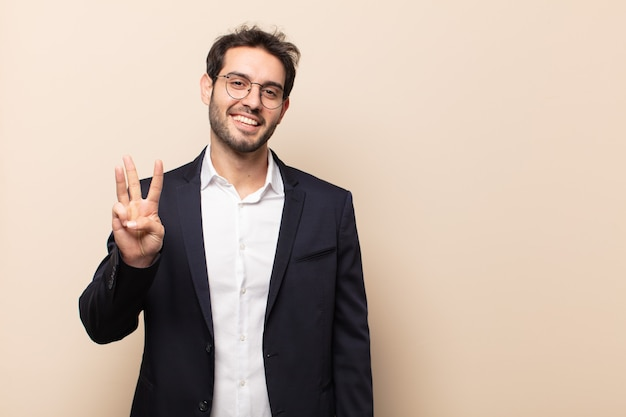 Young handsome man smiling and looking friendly, showing number three or third with hand forward, counting down