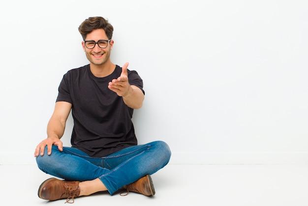 Молодой красивый мужчина улыбается, выглядит счастливым, уверенным и дружелюбным, предлагая рукопожатие, чтобы закрыть сделку, сотрудничая, сидя на полу