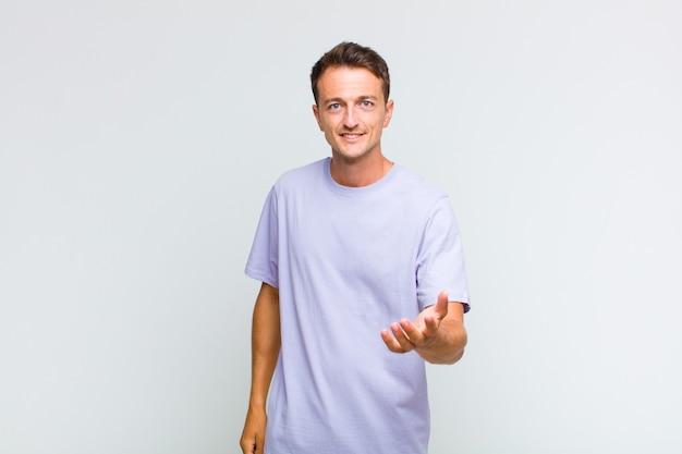 Молодой красивый мужчина улыбается, выглядит счастливым, уверенным и дружелюбным, предлагает рукопожатие, чтобы закрыть сделку, сотрудничает