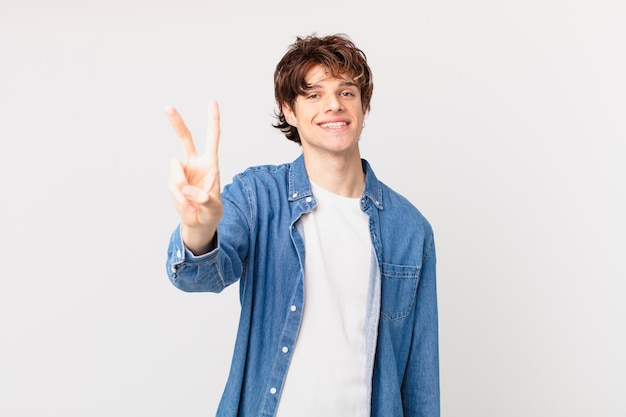Young handsome man smiling and looking happy, gesturing victory or peace