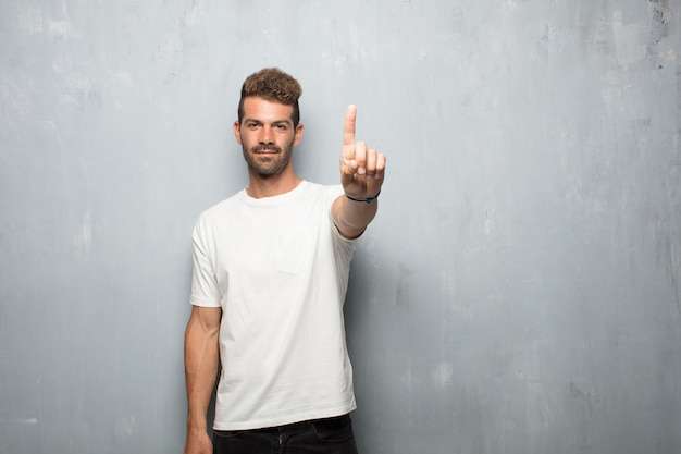 Young handsome man smiling and looking satisfied and happy, counting number with one finger.