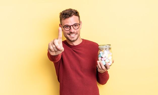 誇らしげにそして自信を持って笑顔でナンバーワンを作っている若いハンサムな男。ゼリーキャンディーのコンセプト