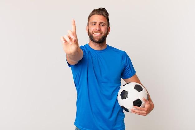 자랑스럽게 웃고 자신있게 넘버 원을 만드는 젊은 잘 생긴 남자. 축구 개념