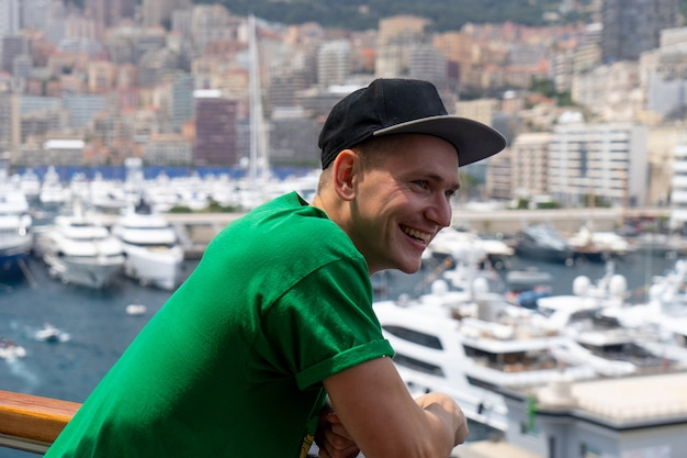 Young handsome man smiling on the ship with blurred sailboats and ships on background. monte carlo, monaco.