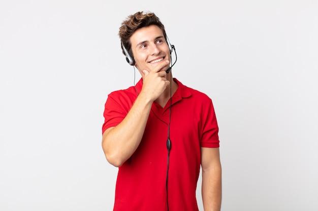 Молодой красивый мужчина улыбается с счастливым, уверенным выражением лица, положив руку на подбородок. концепция телемаркетинга