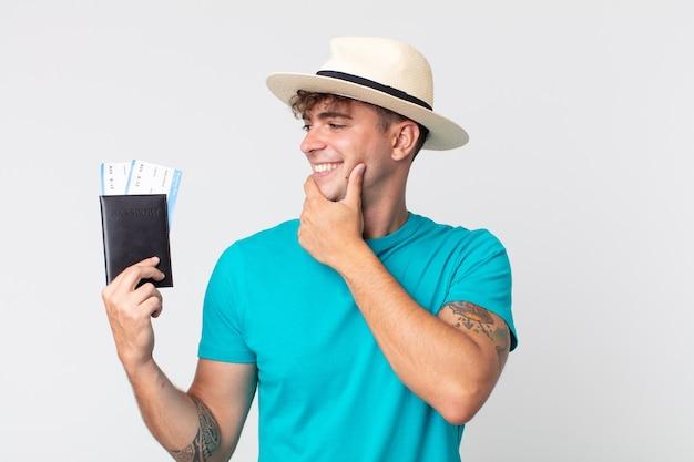턱에 손을 대고 행복하고 자신감 있는 표정으로 웃고 있는 젊고 잘생긴 남자. 여권을 들고 있는 여행자
